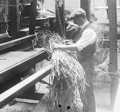A man dealing with a bundle of jute strips at the Abingdon Carpet Company, Abingdon, Oxfordshire
